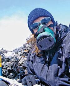 ON THE EDGE Wearing a gas mask, Mather sits on the crater rim of Villarrica Volcano, in Chile, after collecting gas and aerosol samples.
