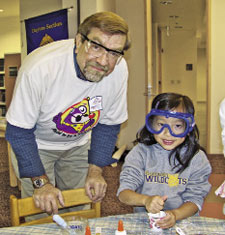 Volunteer Wayne Cook helps a student with an activity during the Dayton Section's library event.