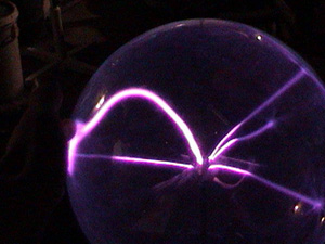 Bogard used argon in his plasma-ball system. Argon produces lavender streamers at low applied voltage.  The streamer at the left is grounded to his fingertip.