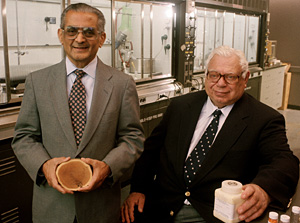 Mansukh C. Wani (left) and Monroe E. Wall of the Research Triangle Institute, in North Carolina, hold a sample of a yew tree, the natural source of Taxol, and a bottle of camptothecin, another natural product that inspired cancer therapies. Wall and Wani were key players in the isolation of both compounds.