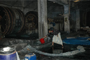 Water Circulation: A tannery worker in sandals stands in chemical-laden water.